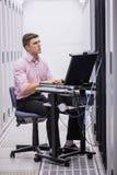 Technicuszitting op draaistoel die laptop met behulp van om servers te diagnostiseren royalty-vrije stock foto's