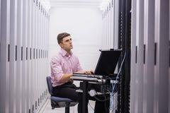 Technicuszitting op draaistoel die laptop met behulp van om servers te diagnostiseren stock fotografie