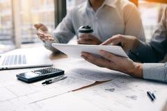Techniek twee die en digitale tablet samenwerken gebruiken die blauwdruk en analyse met architecturaal plan op bureau kijken stock afbeelding
