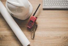 Techniekhulpmiddelen op het werklijst voor bouwproject Met een witte helm, een radio en blauwdrukken Veiligheidscontrole Stock Afbeelding