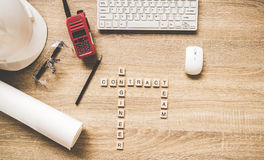 Techniekhulpmiddelen op het werklijst voor bouwproject met een witte helm, een radio en blauwdrukken Woorden van col. van ingenie stock foto