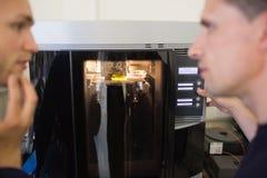 Techniekstudenten die 3d printer met behulp van Stock Afbeeldingen