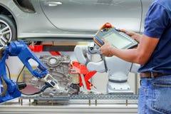 Technik używa bezprzewodowego pilota dla ustawiać program dla kontrolnego przemysłowego robota fotografia stock