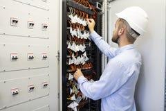 Technika inżynier w datacenter Sieć technika złączony włókno światłowodowe przy serweru pokojem obraz royalty free