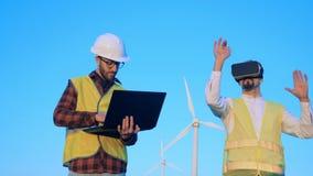 Techniker arbeiten nahe Windmühlen, tragenden VR-Gläsern und dem Schreiben auf einem Laptop Innovatives Technikkonzept stock video