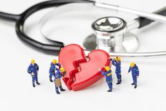 Techniker-Arbeitskraftteam der Miniaturleute nettes mit einheitlicher Hilfsfestlegung oder rotes defektes Herz mit Stethoskop auf stockfotos