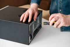 Techniker bauen Computer mit einem Schraubenzieher für Problemdiagnose auseinander stockfoto