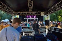 Techniker bei der Arbeit und Leute, die schönes Wetter am Festival genießen und eine Bandausführung aufpassen Lizenzfreie Stockbilder