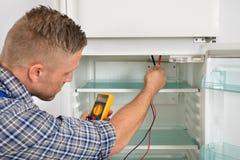 Techniker-Checking Fridge With-Vielfachmessgerät Stockbilder
