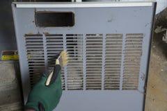 Techniker Cleaning Front Cover Of Furnace Lizenzfreie Stockfotografie