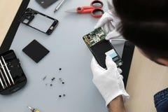 Techniker, der bei Tisch defekten Smartphone repariert lizenzfreie stockfotos