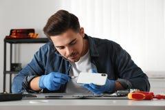 Techniker, der bei Tisch defekten Smartphone repariert lizenzfreies stockfoto