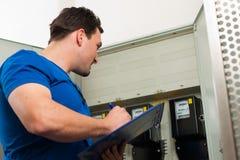 Techniker, der das Elektrizitätsmeßinstrument liest Stockfotos