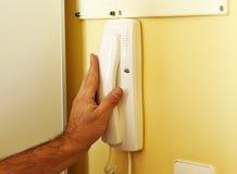 Techniker, der das neue Wechselsprechanlagentelefon innerhalb des Hauses setzt Lizenzfreie Stockbilder