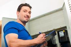 Techniker, der das Strommeter liest lizenzfreie stockfotografie