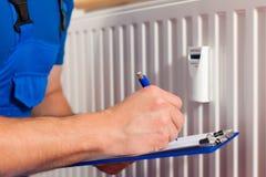 Techniker, der den Wärmemengenzähler liest Lizenzfreie Stockbilder