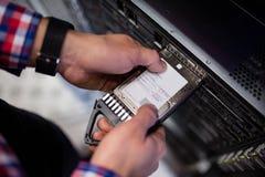 Techniker, der ein Festplattenlaufwerk in einen Blattserver einfügt Stockfoto