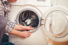 Techniker, der eine Waschmaschine repariert Lizenzfreie Stockfotografie