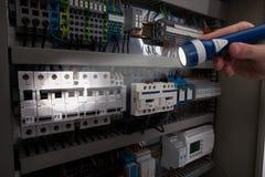 Techniker, der fusebox mit Taschenlampe analysiert lizenzfreies stockbild