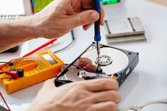 Techniker, der gebrochenes Festplattenlaufwerk repariert Stockbild