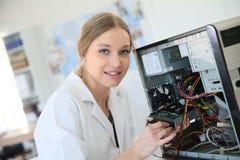 Techniker der jungen Frau, der Computer repariert Stockbild