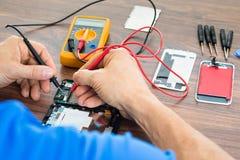Techniker, der Mobiltelefon mit Vielfachmessgerät repariert stockfotografie