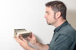 Techniker, der Thermostatabdeckung entfernt Stockbild