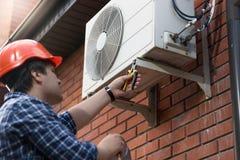 Techniker im Hardhat, der Klimaanlage im Freien anschließt stockbilder