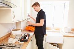 Techniker Instandhaltungsboilerâin der Küche unter Verwendung des Tablet-Computers stockbild