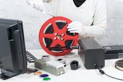 Techniker mit weißen Handschuhen einen 16mm Film digitalisierend Lizenzfreie Stockbilder
