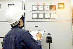 Techniker notiert Datenspannung oder -strom im Bedienfeld Lizenzfreies Stockbild