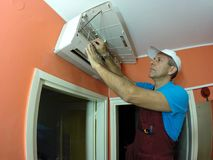 Techniker Remove And Clean der Filter der Luft Conditione lizenzfreie stockfotografie