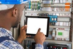 Techniker Using Digital Tablet bei der Untersuchung von Fusebox stockfotografie