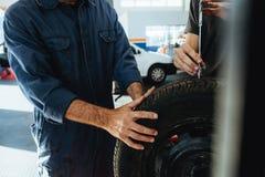 Techniker, welche die Tiefe des Reifenschrittinstrumentes messen lizenzfreie stockfotos