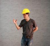 Technikermannwaren färben Sturzhelm mit der dunkelgrauen T-Shirt und Denimjeans-Stellung und -Handzeichen, als ob, um etwas zu fa Lizenzfreie Stockfotografie