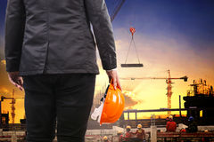 Technikmann, der Schutzhelm hält und wenn Co arbeitet, errichtet wird Lizenzfreie Stockbilder