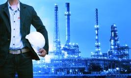 Technikmann und -Schutzhelm, die gegen Erdölraffinerie stehen