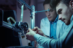 Technikteam, das an einem Drucker 3D arbeitet Stockfotos