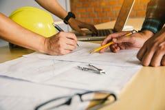 Technikteams treffen sich, um constructio darzustellen und zu besprechen Stockbild