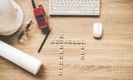 Technikwerkzeuge auf Arbeitstabelle für Bauvorhaben mit einem weißen Sturzhelm, einem Radio und Plänen Wörter von Ingenieurkonzep Stockfoto