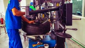 Technique pendant l'assembleur de pneu au centre de service de pneu image stock