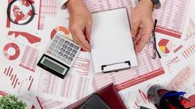 Technique visuelle de présentation La vue de surface plane de l'homme d'affaires travaillant et calculant des finances, lit et ré banque de vidéos