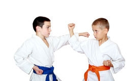 Techniques blows and protection training sportsmen in a kimono Royalty Free Stock Images