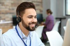 Technische ondersteuningexploitant die met hoofdtelefoon werken stock fotografie