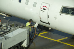 Technitian working below a passenger airplane. Stock Photography