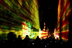 Techno party. Silhouetted crowd at techno party completed with laser projections Stock Images