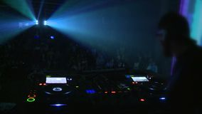 Techno party DJ. Techno party. People dance, DJ playing music. Everywhere colored lights stock footage