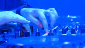 DJ console. Techno party. People dance, DJ playing music. Everywhere colored lights stock video