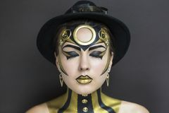 Techno woman. Techno golden girl with bright makeup. Streams of gold, shiny cheeks, black steam punk hat, big circle on forehead, body art. Sexy lips Royalty Free Stock Photography