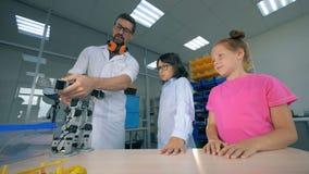 Technolgies de la robótica del estudio del profesor de ciencias de la escuela con los alumnos elegantes Concepto moderno de la ed metrajes
